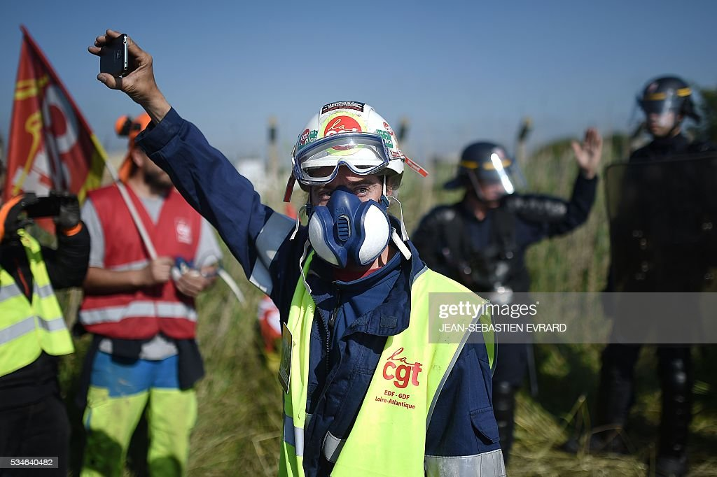 Workers on strike are evacuated by riot police as they block the access to an oil depot near the Total refinery of Donges, western France, on May 27, 2016 to protest against the government's planned labour law reforms. France's Socialist government has bypassed parliament and rammed through a labour reform bill that has sparked two months of massive street protests. / AFP / JEAN