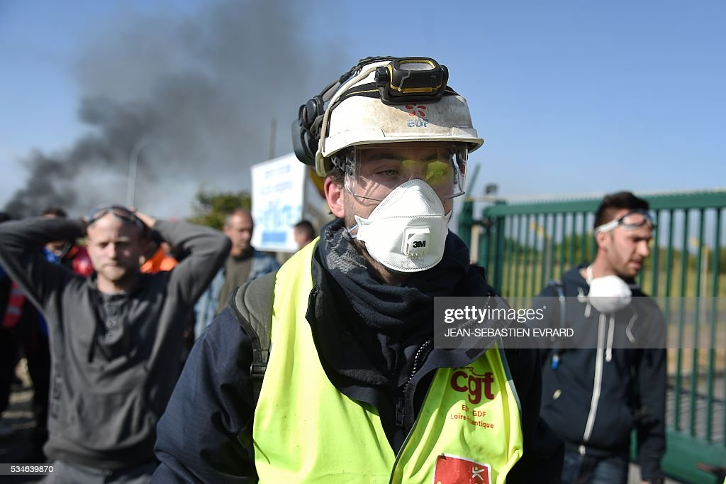 Workers on strike are evacuated by riot police as they were blocking the access to an oil depot near the Total refinery of Donges, western France, on May 27, 2016 to protest against the government's planned labour law reforms. France's Socialist government has bypassed parliament and rammed through a labour reform bill that has sparked two months of massive street protests. / AFP / JEAN