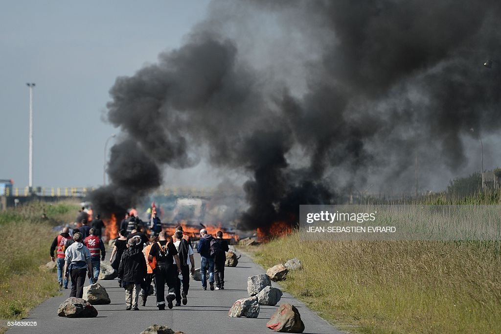 Workers on strike are evacuated by riot policemen as they block the access to an oil depot near the Total refinery of Donges, western France, on May 27, 2016 to protest against the government's planned labour law reforms. The French government's labour market proposals, which are designed to make it easier for companies to hire and fire, have sparked a series of nationwide protests and strikes over the past three months. French unions on May 27 called on workers to 'continue and step up their action', as a wave of strikes against a disputed labour law disrupted transport and fuel supplies. / AFP / JEAN