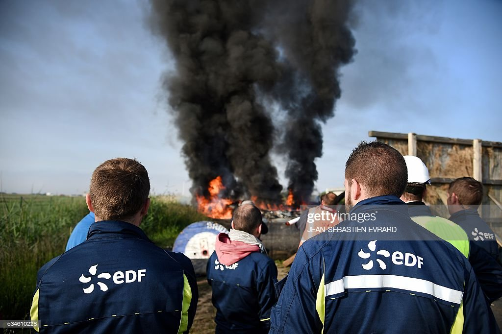Workers on strike block the access to an oil depot near the Total refinery of Donges, western France, on May 27, 2016 to protest against the government's planned labour law reforms. France's Socialist government has bypassed parliament and rammed through a labour reform bill that has sparked two months of massive street protests.protests. / AFP / JEAN