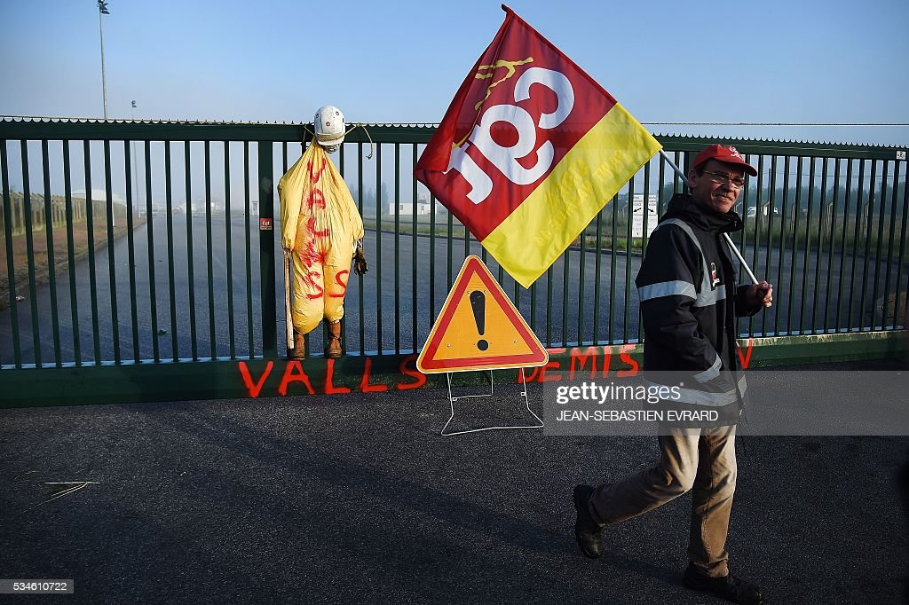 Workers on strike block the access to an oil depot near the Total refinery of Donges, western France, on May 27, 2016 to protest against the government's planned labour law reforms. France's Socialist government has bypassed parliament and rammed through a labour reform bill that has sparked two months of massive street protests. / AFP / JEAN