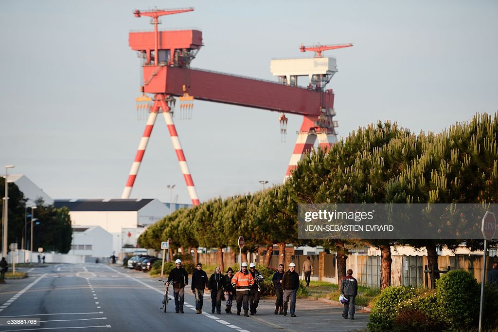 Workers on strike block the access to the harbour of Saint-Nazaire, western france, on May 24, 2016 to protest against the government's planned labour law reforms. Petrol shortages caused long tailbacks of motorists in parts of France on May 23 as protesters angry over government labour reforms blockaded some of the country's oil refineries and fuel depots. The action was the latest in three months of strikes and protests against the reform, which has set the Socialist government against some of its traditional supporters and sometimes sparked violence. / AFP / JEAN