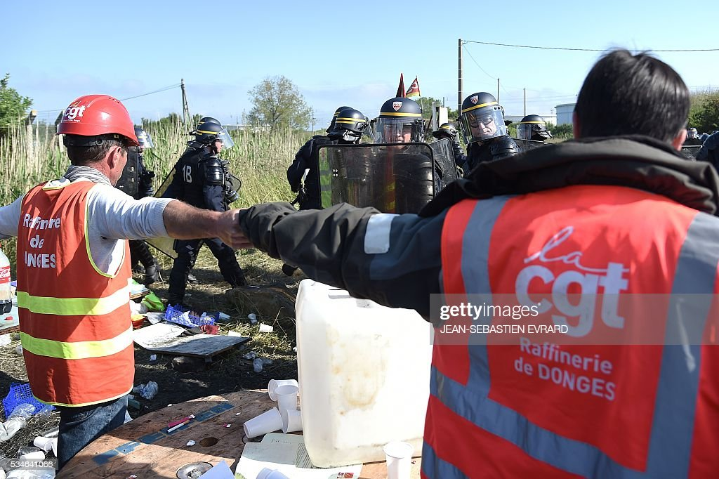 Workers on strike hold hands in front of French riot policemen to block the access to an oil depot near the Total refinery of Donges, western France, to protest against the government's planned labour law reforms, on May 27, 2016. The French government's labour market proposals, which are designed to make it easier for companies to hire and fire, have sparked a series of nationwide protests and strikes over the past three months. French unions on May 27 called on workers to 'continue and step up their action', as a wave of strikes against a disputed labour law disrupted transport and fuel supplies. / AFP / JEAN