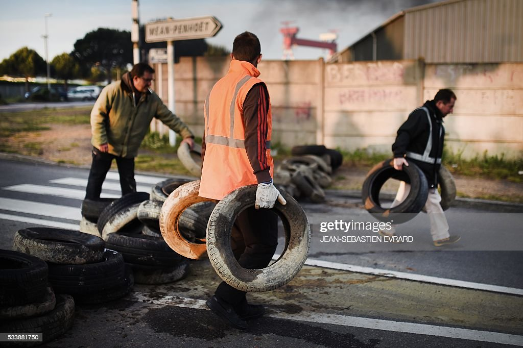 Workers on strike install a barricade with tyres to block the access to the harbour of Saint-Nazaire, western france, on May 24, 2016 to protest against the government's planned labour law reforms. Petrol shortages caused long tailbacks of motorists in parts of France on May 23 as protesters angry over government labour reforms blockaded some of the country's oil refineries and fuel depots. The action was the latest in three months of strikes and protests against the reform, which has set the Socialist government against some of its traditional supporters and sometimes sparked violence. / AFP / JEAN