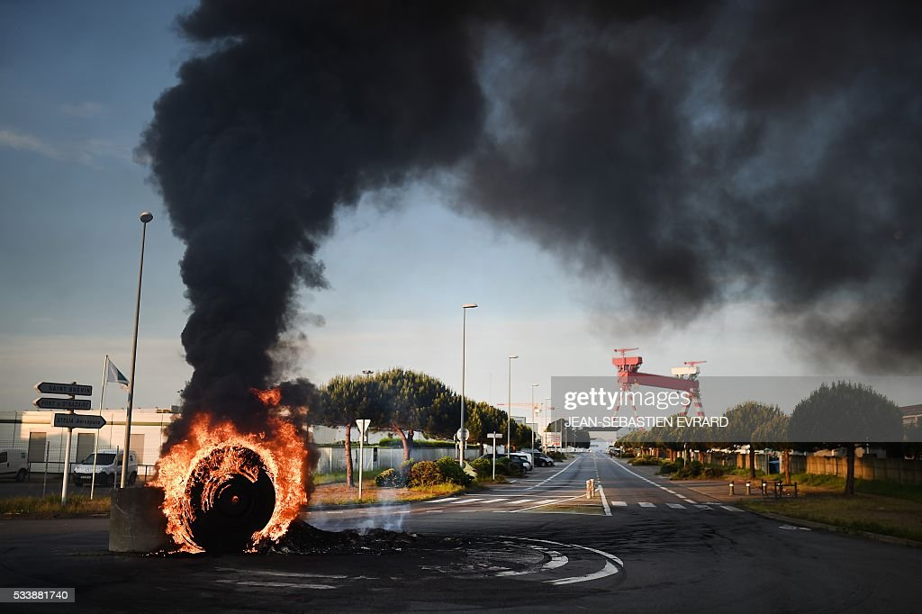 Workers on strike set up a burning barricade to block the access to the harbour of Saint-Nazaire, western france, on May 24, 2016 to protest against the government's planned labour law reforms. Petrol shortages caused long tailbacks of motorists in parts of France on May 23 as protesters angry over government labour reforms blockaded some of the country's oil refineries and fuel depots. The action was the latest in three months of strikes and protests against the reform, which has set the Socialist government against some of its traditional supporters and sometimes sparked violence. / AFP / JEAN