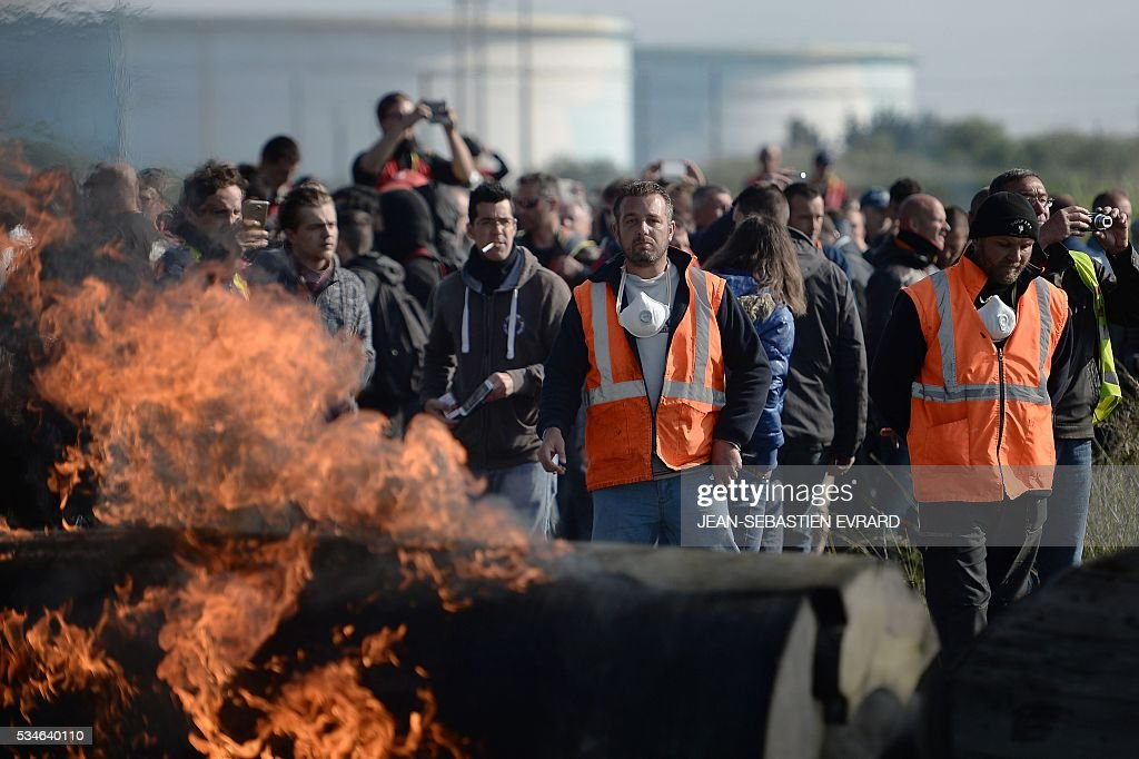 Workers on strike set up a fire barricade to block the access to an oil depot near the Total refinery of Donges, western France, to protest against the government's planned labour law reforms, on May 27, 2016. The French government's labour market proposals, which are designed to make it easier for companies to hire and fire, have sparked a series of nationwide protests and strikes over the past three months. French unions on May 27 called on workers to 'continue and step up their action', as a wave of strikes against a disputed labour law disrupted transport and fuel supplies. / AFP / JEAN