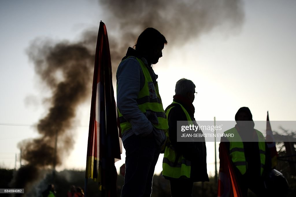 Workers on strike stand as they block the access to an oil depot near the Total refinery of Donges, western France, on May 27, 2016 to protest against the government's planned labour law reforms The French government's labour market proposals, which are designed to make it easier for companies to hire and fire, have sparked a series of nationwide protests and strikes over the past three months. French unions on May 27 called on workers to 'continue and step up their action', as a wave of strikes against a disputed labour law disrupted transport and fuel supplies. / AFP / JEAN