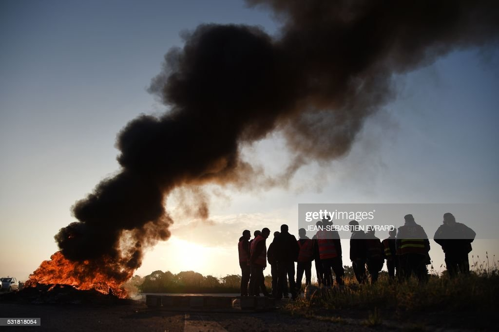TOPSHOT Workers on strike stand next to burning tyres as they block the access to the Total refinery of Donges western france on May 17 2016 to...
