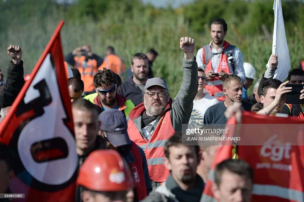 Workers on strike walk as they are evacuated by riot police after blocking the access to an oil depot near the Total refinery of Donges, western France, on May 27, 2016 to protest against the government's planned labour law reforms. France's Socialist government has bypassed parliament and rammed through a labour reform bill that has sparked two months of massive street protests. / AFP / JEAN