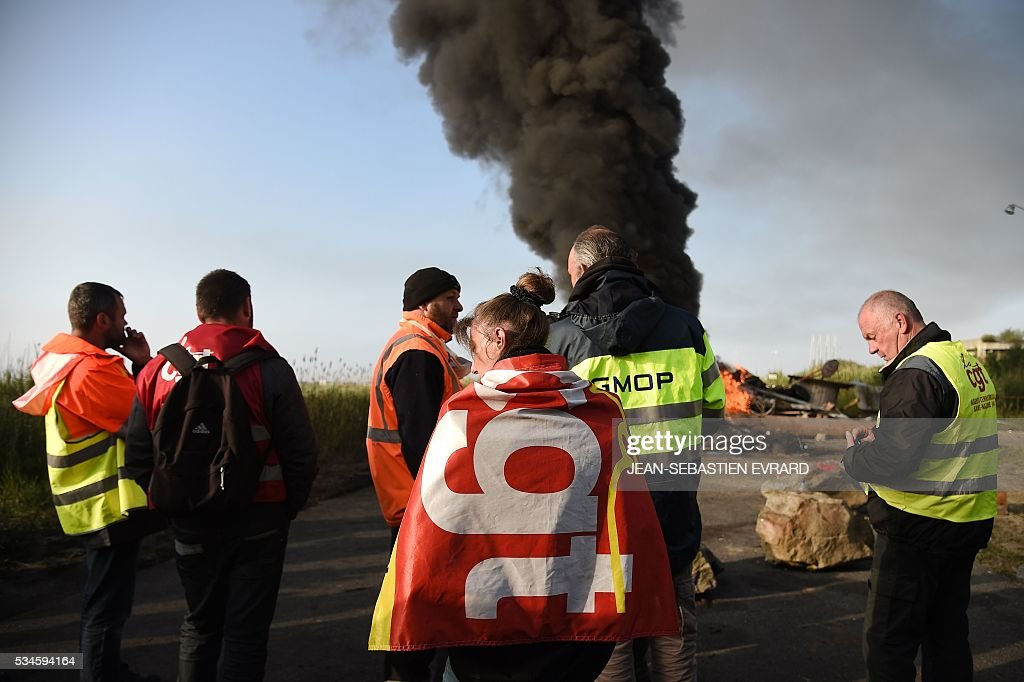Workers on strike wrapped in French CGT union's flags stand as they block the access to an oil depot near the Total refinery of Donges, western France, on May 27, 2016 to protest against the government's planned labour law reforms The French government's labour market proposals, which are designed to make it easier for companies to hire and fire, have sparked a series of nationwide protests and strikes over the past three months. French unions on May 27 called on workers to 'continue and step up their action', as a wave of strikes against a disputed labour law disrupted transport and fuel supplies. / AFP / JEAN