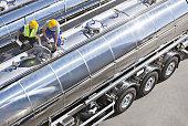 Workers on top of stainless steel milk tanker
