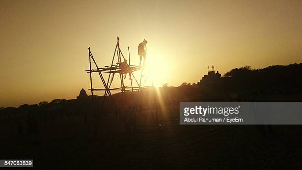 Workers On Wooden Frame During Sunset
