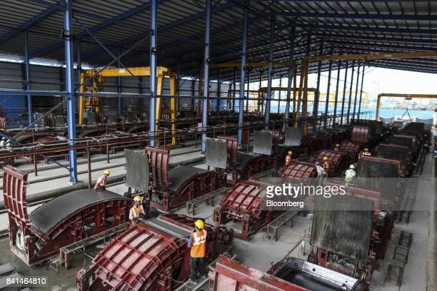 Workers open the molds of precast concrete tunnel segment at the Mumbai Metro Rail Corp casting yard in Mumbai India on Monday Aug 28 2017 The...