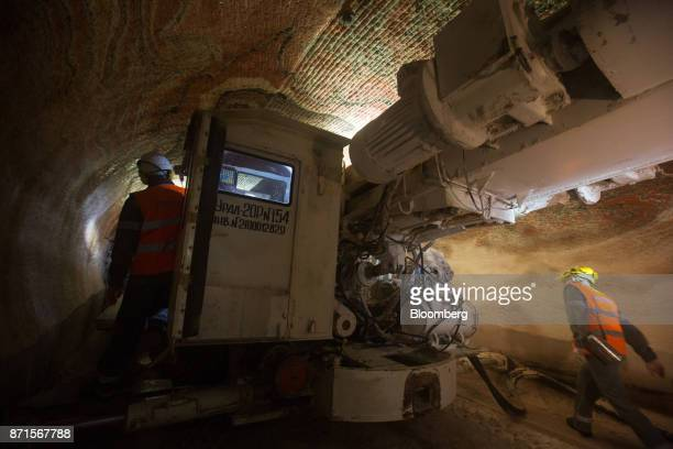 Workers operate a rock drilling machine during excavations for sylvinite mineral ore used to produce potash fertilizer in the underground potash mine...