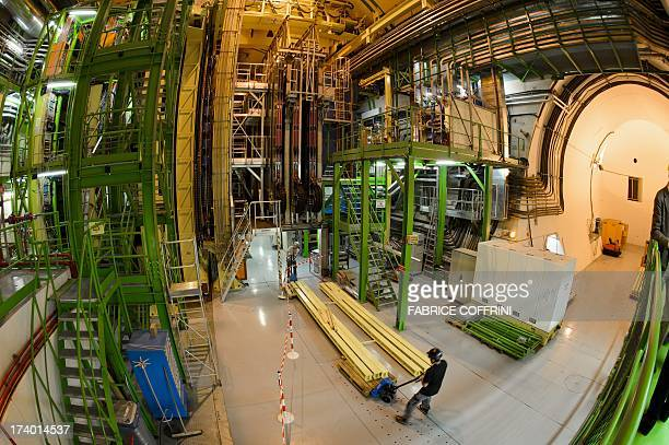 Workers operate at the CERN's Large Hadron Collider beauty experiment during maintenance works on July 19 2013 in Meyrin near Geneva Tests at the...