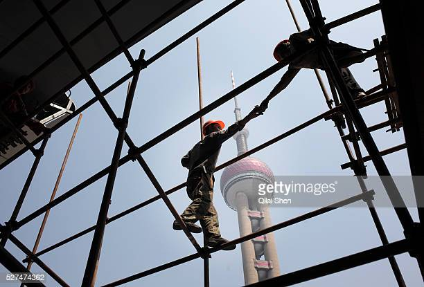 Workers operate on a scaffolding at a construction site in the middle of the Lujiazui Financial District with the iconic Pearl Oriental TV Tower in...