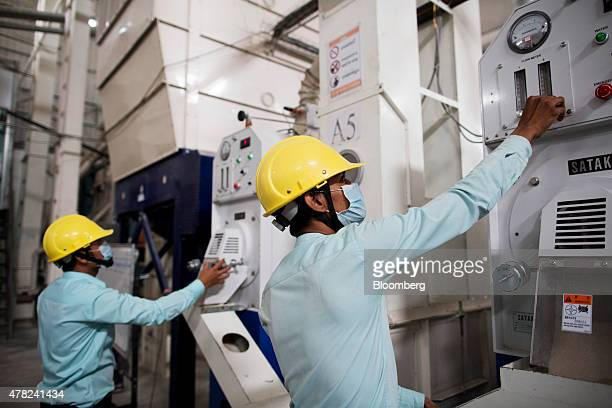 Workers operate rice polishing machines at the Amru Rice Co processing factory in Phnom Penh Cambodia on Monday June 22 2015 The 10 members of the...
