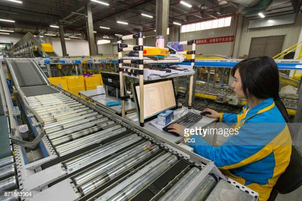 Workers operate the conveyor at the intelligent warehouse 'Suning cloud warehouse' of China's retail giant Suning on November 8 2017 in Nanjing...