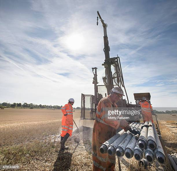 Workers operating drilling rig in field
