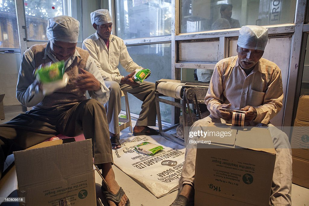 Workers pack one-kilogram sugar packets into boxes in the packaging unit of the Simbhaoli Sugars Ltd. mill in Ghaziabad, Uttar Pradesh, India, on Tuesday, Feb. 26, 2013. India, the world's biggest sugar producer, plans to seek a consensus among various ministries on ending four-decade old state controls on the domestic industry, Food Minister K.V. Thomas said. Photographer: Prashanth Vishwanathan/Bloomberg via Getty Images