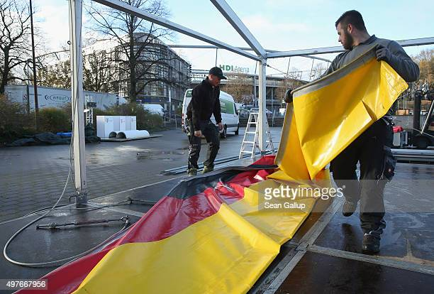 Workers pack up a tent in the colors of the German flag the day after the Germany vs Netherlands friendly football match was cancelled due to a...