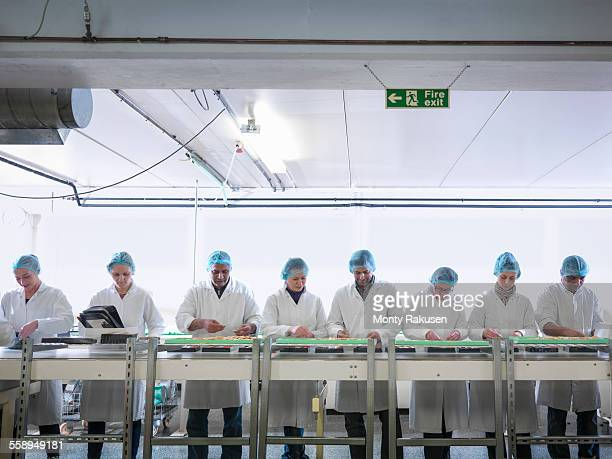 Workers packing chocolates on production line in chocolate factory