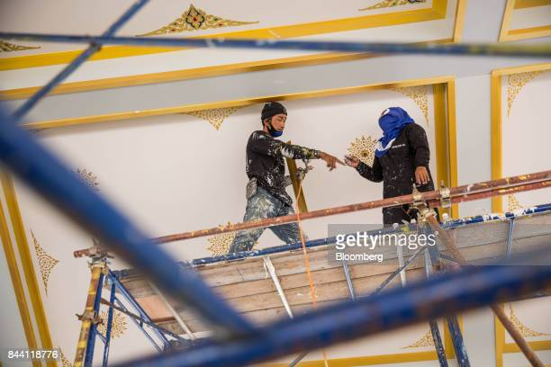 Workers paint a ceiling while preparing the ceremonial ground for King Bhumibol Adulyadej's cremation at Sanam Luang park in Bangkok Thailand on...