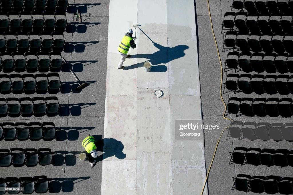 Workers paint a walkway outside the U.S. Capitol prior to the second inauguration of U.S. President Barack Obama in Washington, D.C., U.S., on Friday, Jan. 18, 2013. President Obama's second inauguration next week will combine the star power of Beyonce, Kelly Clarkson and James Taylor with a lineup that reflects social values Obama will champion in his new term. Photographer: Andrew Harrer/Bloomberg via Getty Images
