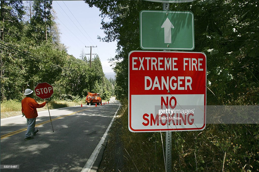 Workers paint on State Highway 18 near a sign warning of extreme fire danger on August 1, 2005 near Crestline, west of Lake Arrowhead, California. Last winter was one of the wettest on record, dropping 90 inches of rain in some southern California mountain areas and creating the thickest vegetation growth in memory, and damaging more than 2,000 miles of fire access roads used to protect 2.3 million acres of forests. In addition to the many thousands of trees killed by a massive pine beetle infestation, newly grown vegetation is drying up under triple-digit temperatures and raising fears of a repeat of the devastating fire season of 2003. President Bush signed an emergency funding bill in May allocating $25 million to fix roads in southern California?s national forests but Congress has acted slower than expected in providing the money so some of the repairs might not be done until October.