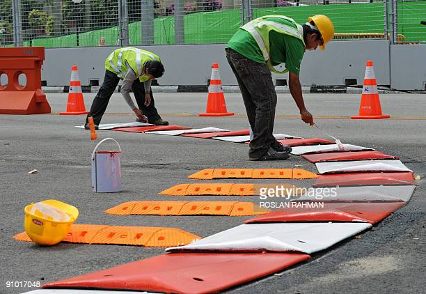 Workers paint the curb line of the road that will be used as the circuit for the upcoming Singapore Formula One night race in Singapore on September...