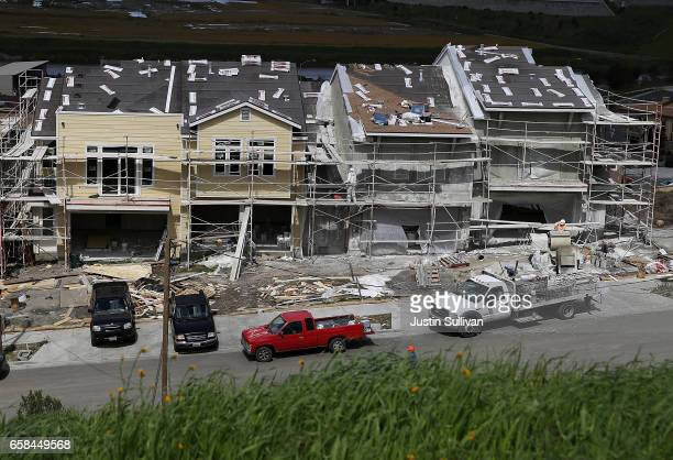 Workers paint the exterior of a new home at a housing development on March 27 2017 in Petaluma California According to a study by real estate...