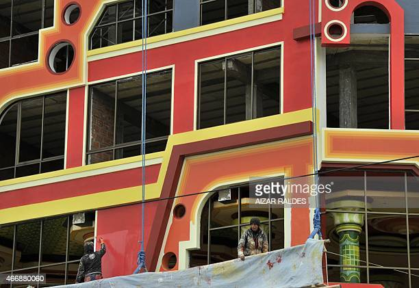 Workers paint the façade of a building built in neoAndean baroque architecture known as Cholet style in El Alto Bolivia on March 13 2015 The...
