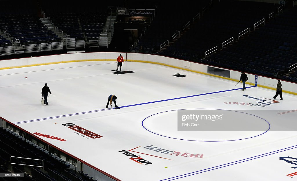 Workers paint the ice and put down logos for the Washington Capitals at Verizon Center on January 9, 2013 in Washington, DC.