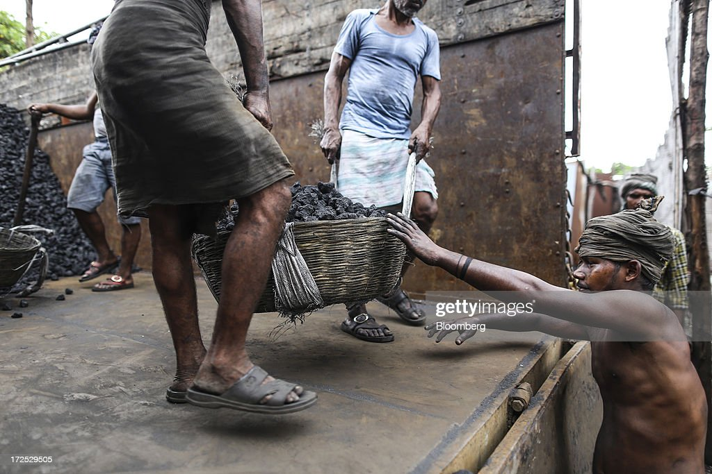 Workers pass a basket of coal to a fellow worker during the unloading of a truck at a coal wholesale market in Mumbai, India, on Tuesday, July 2, 2013. India, the worlds third-largest coal consumer, imported 43 percent more of the fuel than a year ago on increased demand from power stations and steelmakers, according to shipping data, and is set to eclipse China as the top importer of power station coal by 2014. Photographer: Dhiraj Singh/Bloomberg via Getty Images