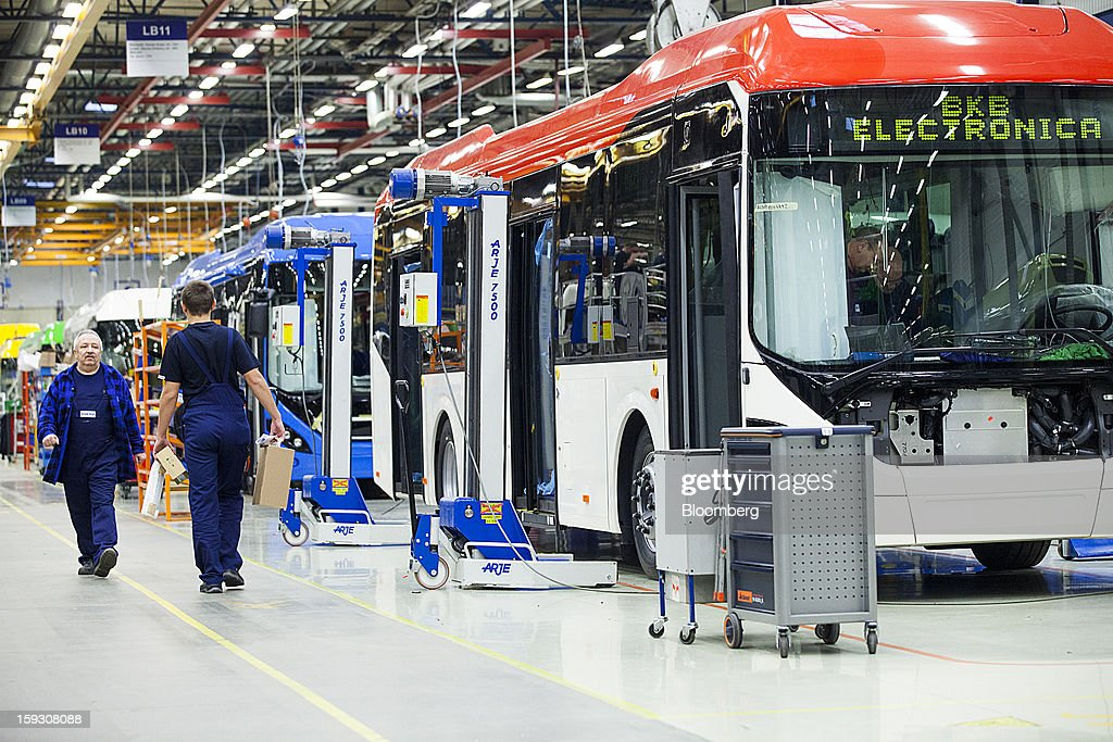 Workers pass Arje Sweden AB 7500 vehicle hoists, center, on the bus production line during assembly at Volvo AB's manufacturing plant in Wroclaw, Poland, on Friday, Jan. 11, 2013. Volvo plans to end bus making in Saeffle by June 2013, and will consolidate the business in Europe to its main plant in Wroclaw, Poland, the Gothenburg, Sweden-based company said. Photographer: Bartek Sadowski/Bloomberg via Getty Images