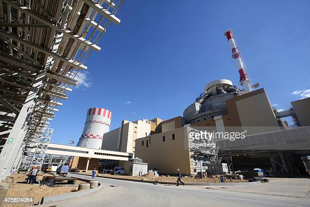 Workers pass by a new power unit under construction at the Novovoronezh NPP2 nuclear power station operated by OAO Rosenergoatom a unit of Rosatom...
