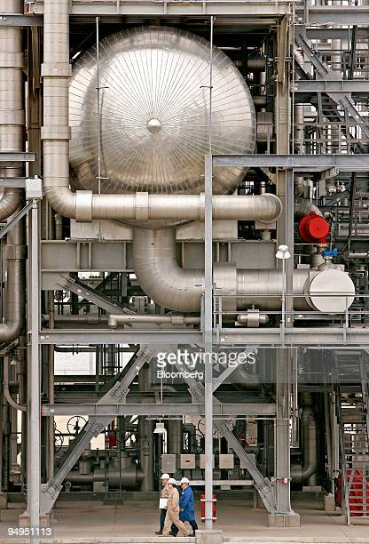 Workers pass by the vaporizer structure with tube and shell exchangers at the Freeport LNG facility in Quintana Texas US on Wednesday April 1 2009...