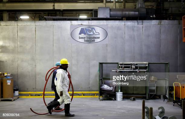 Workers pass in front of signage at the Automatic Coating Ltd facility in Toronto Ontario Canada on Wednesday Jan 11 2017 Statistics Canada is...