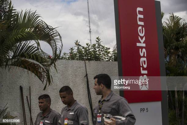 Workers pass in front of signage displayed outside the Braskem SA petrochemical plant in Duque de Caxias Brazil on Friday Aug 4 2017 Petroleo...