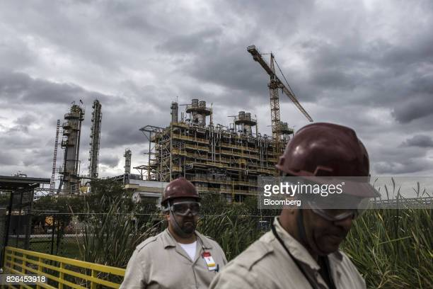 Workers pass in front of the Braskem SA petrochemical plant in Duque de Caxias Brazil on Friday Aug 4 2017 Petroleo Brasileiro SA and Odebrecht SA...
