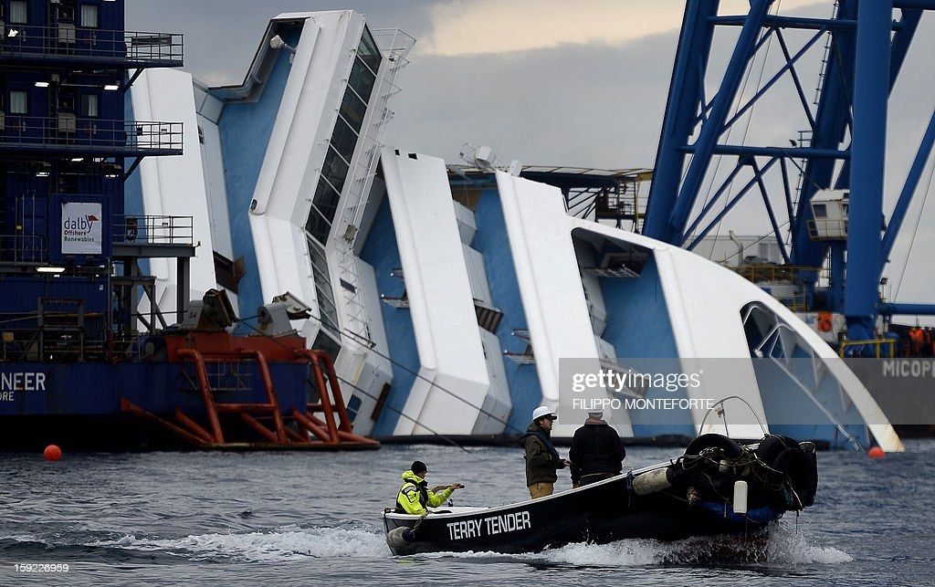 Workers pass on a small boat near the Costa Concordia cruise ship laying aground near the port on January 10, 2013 on the Italian island of Giglio. A year on from the Costa Concordia tragedy in which 32 people lost their lives, the giant cruise ship still lies keeled over on an Italian island and its captain Francesco Schettino has become a global figure of mockery.