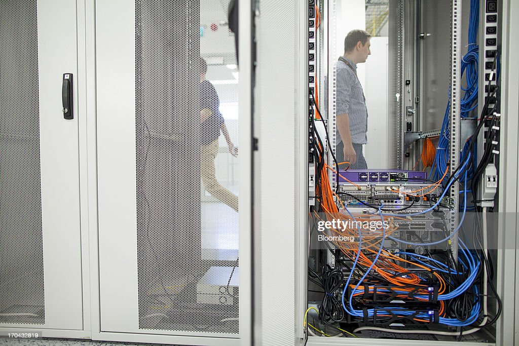 Workers pass telecommunications equipment in the information technology (IT) centre of Orange Polska, also known as Telekomunikacja Polska SA (TPSA), Poland's national telecommunications company, in Warsaw, Poland, on Wednesday, June 12, 2013. Cable providers are being drawn to Poland, the European Union's biggest eastern economy, because penetration levels are half that of neighboring Germany even as unemployment rises, according to a website presentation by the country's biggest TV network, Cyfrowy Polsat SA. Photographer: Bartek Sadowski/Bloomberg via Getty Images