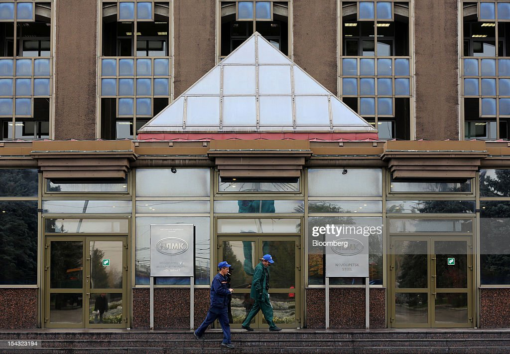 Workers pass the entrance to administrative offices at the OAO Novolipetsk Steel plant, also known as NLMK, in Lipetsk, Russia, on Wednesday, Oct. 17, 2012. OAO Novolipetsk Steel, controlled by billionaire Vladimir Lisin, became Russia's largest steelmaker by output after boosting production by 24 percent. Photographer: Andrey Rudakov/Bloomberg via Getty Images