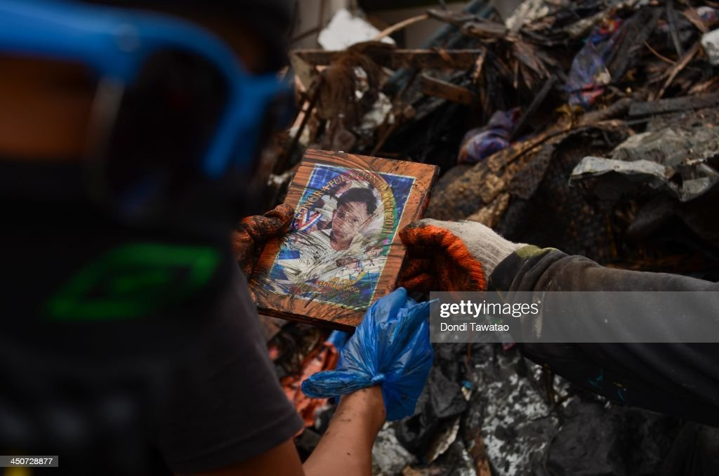 Workers pause to look at a portrait of a boy on November 20 2013 in Tacloban Leyte Philippines Typhoon Haiyan which ripped through the Philippines on...