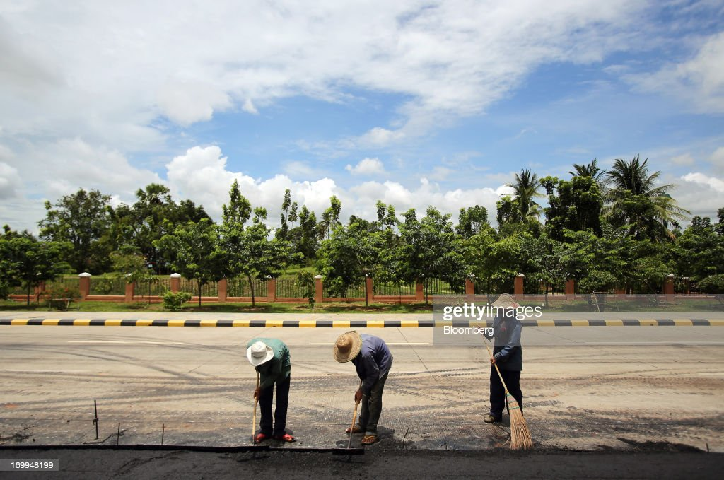 Workers pave a section of a highway under construction in Naypyidaw, Myanmar, on Wednesday, June 5, 2013. Myanmar hosts the three-day World Economic Forum on East Asia starting today, with heads of state and executives from companies including General Electric Co., Coca-Cola Co. and WPP Plc attending. Photographer: Dario Pignatelli/Bloomberg via Getty Images