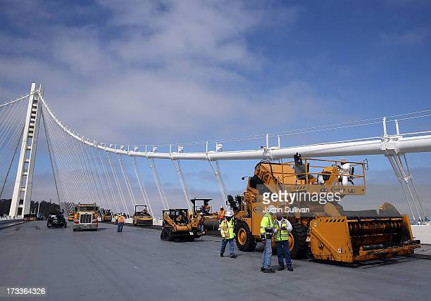 Workers pave the deck of the new eastern span of the newly constructed San FranciscoOakland Bay Bridge on July 12 2013 in Oakland California Workers...