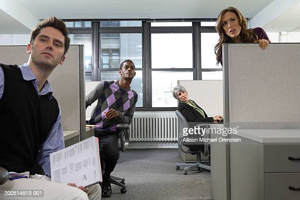 Workers peeking from cubicles