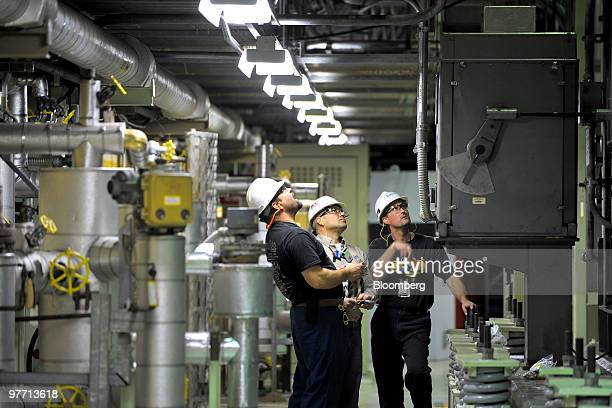 Workers perform routine maintenance on plumbing equipment underneath the number two reactor at Exelon Corp's Limerick nuclear power generating...