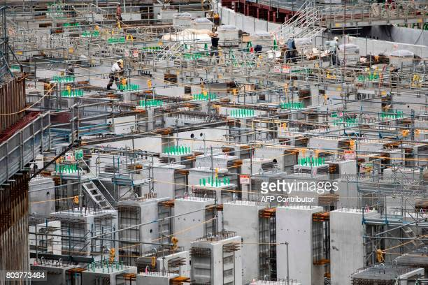 Workers perform their duties at the construction site for the National Stadium venue for the upcoming Tokyo 2020 Olympics in Tokyo on June 30 2017...