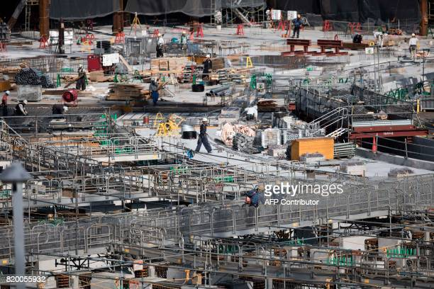 Workers perform their duties at the construction site for the National Stadium venue for the upcoming Tokyo 2020 Olympic Games in Tokyo on July 21...